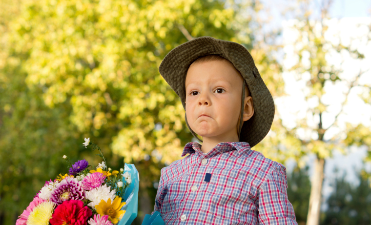 Bemused little boy with flowers