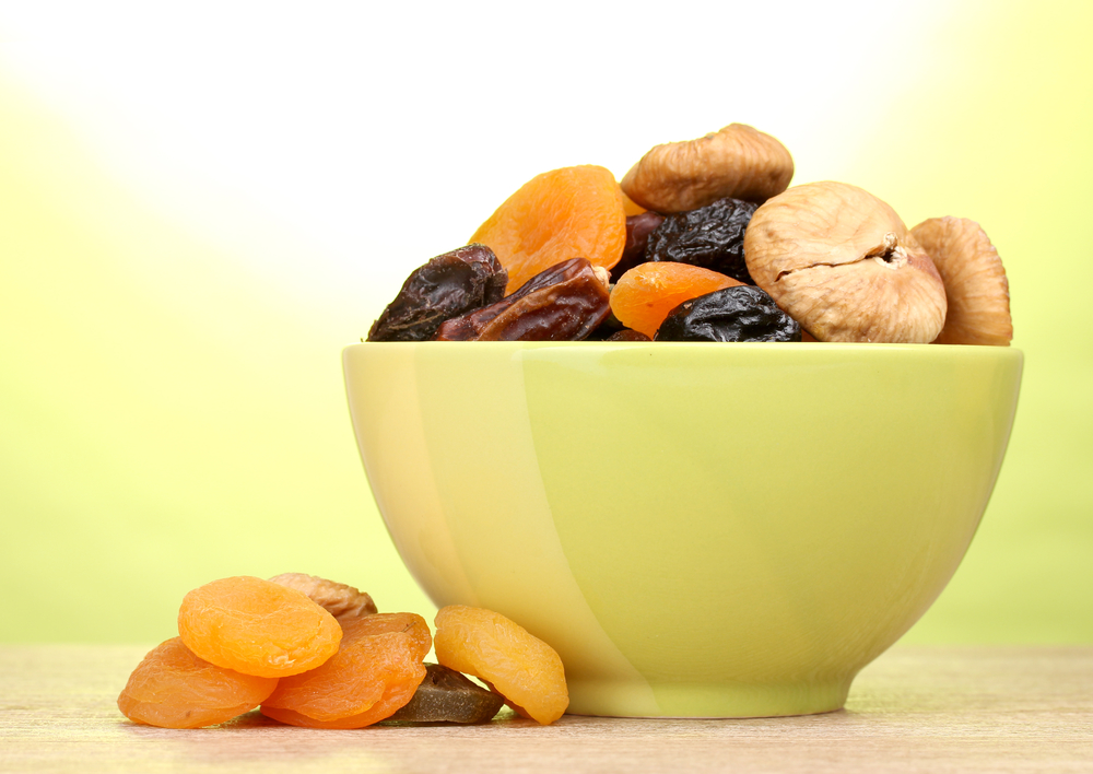 Dried fruits in green bowl on wooden table on green background