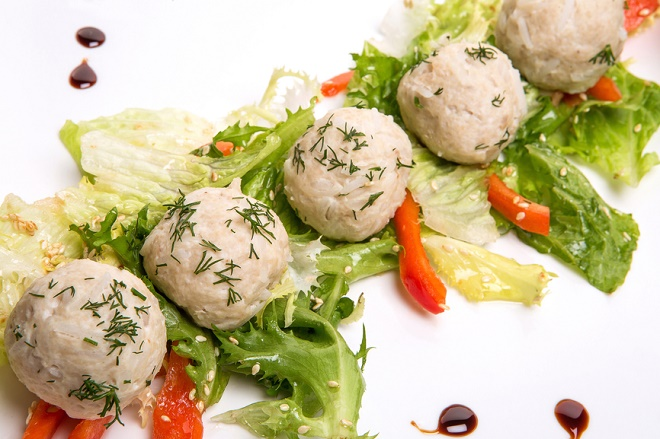 rice patties and salad in a square dish on white